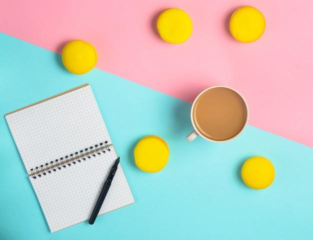ペンと一杯のコーヒーと黄色のマカロンのノート。ミニマリズムのトレンド。上面図。フラット横たわっていた。