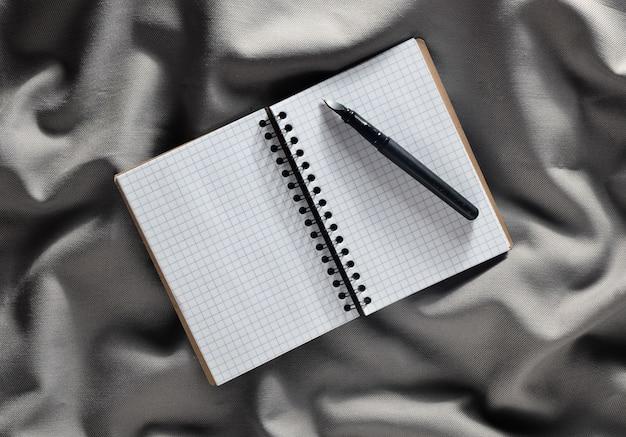 灰色の生地のシルクにメモ帳とペン。上面図。