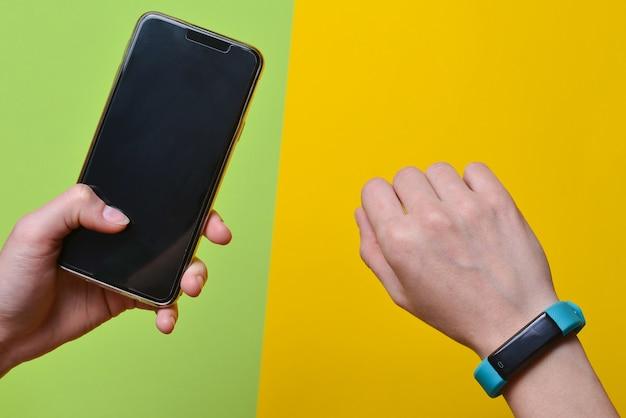 Умные часы на запястье и смартфон в руке синхронизируются. фитнес-браслет современные технологии.