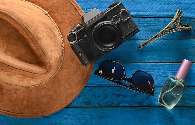 フランス、パリへの旅。フェルトの帽子、フィルムカメラ、サングラス、香水瓶、色付きの木製のテーブルにエッフェル塔のレイアウトのお土産像。旅行、放浪癖のコンセプトへの情熱。フラット横たわっていた。
