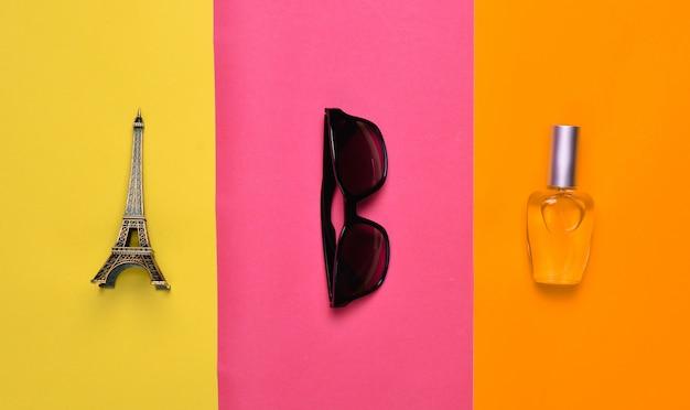 Модные аксессуары и сувениры. статуэтка эйфелевой башни, солнцезащитные очки, флакон духов. минималистский тренд. вид сверху.