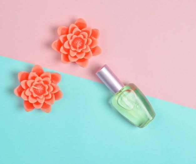 香水瓶と花の形のキャンドルのフラット横たわるミニマリズム。ロマンチックなコンセプトです。