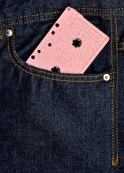 Розовая аудиокассета в переднем кармане джинсов.