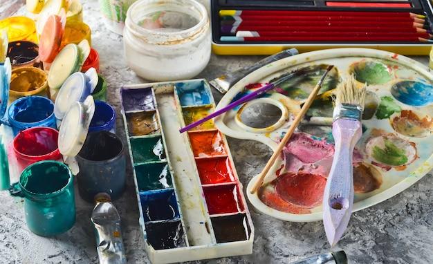 絵画を描くための芸術的なツール。パレット、ガッシュ、油絵の具、ブラシ、色のクレヨン、パステル、色鉛筆。