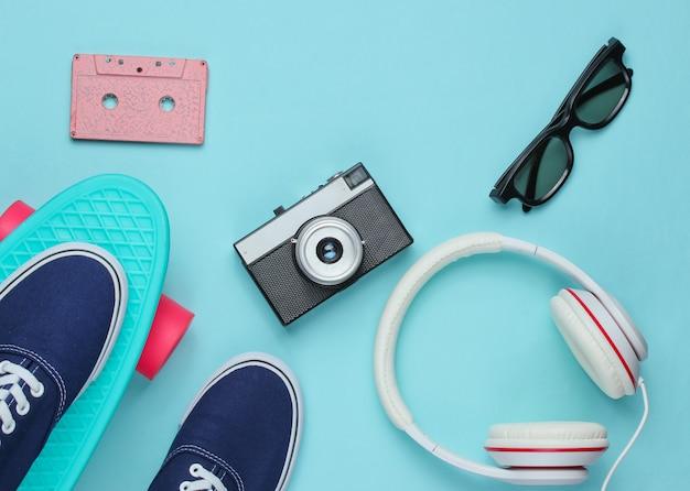 Битник наряд. скейтборд с наушниками, аудиокассетой, ретро-камерой и кроссовками на синей стене