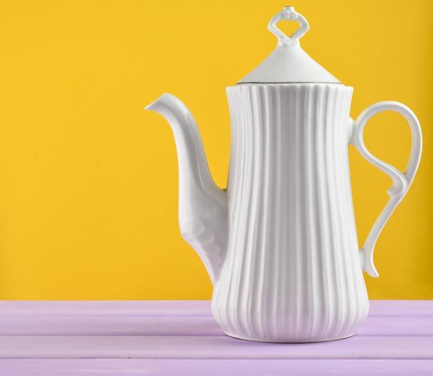 Белый керамический чайник на пастельный фиолетовый деревянный стол изолированы.