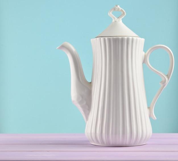 Белый керамический чайник на пастельный фиолетовый деревянный стол изолированы. копировать пространство
