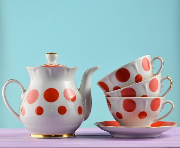 Керамический чайник, стопка чашек в горошек на деревянном столе изолированы. копировать пространство