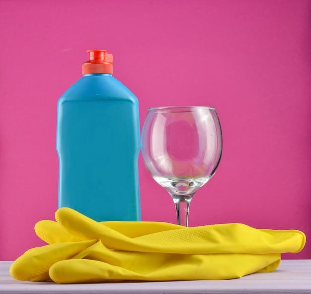 食器洗いやハウスクリーニング用のアクセサリー。食器洗い。洗剤、ガラス、黄色のゴム手袋のボトル