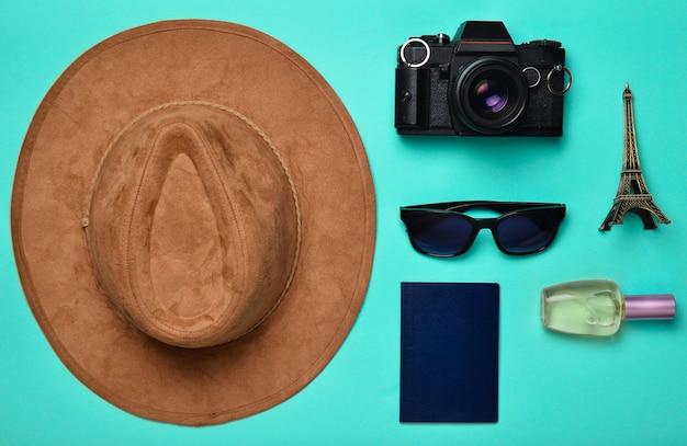 Страсть к путешествиям, страсть к путешествиям. поездка во францию, париж. фетровая шляпа, пленочная камера, солнцезащитные очки, паспорт, флакон духов, сувенирная статуэтка макета эйфелевой башни.