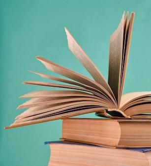 開いた本、分離された書籍のスタック。コピースペース、パステルカラートレンド