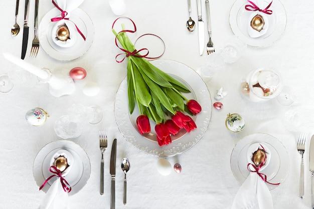 イースターお祝い春のテーブルの設定の装飾、巣の中の卵、新鮮な赤いチューリップ