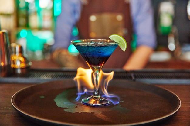 ガラスのゴブレット、アルコールで火を燃やすライムとカクテル