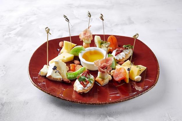 Тапас из белого хлеба с ветчиной и огурцами, с томатным соусом и сыром, лежащий на тарелке
