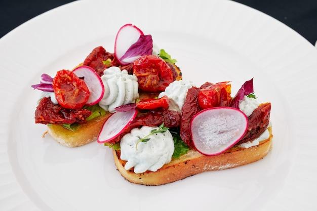 Два бутерброда с овощами лежат на белой тарелке, с редькой, помидорами, перцем, чесноком, зеленью и белым хлебом