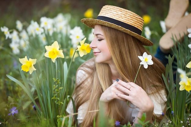 庭の水仙の花と麦わら帽子の美しい女性の肖像画。園芸。