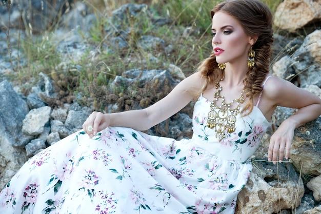 Фасонируйте внешнее фото красивой женщины с темными волосами оплеток в роскошном белом платье представляя в поле лета. невеста. красивая девушка бохо, глядя в сторону.