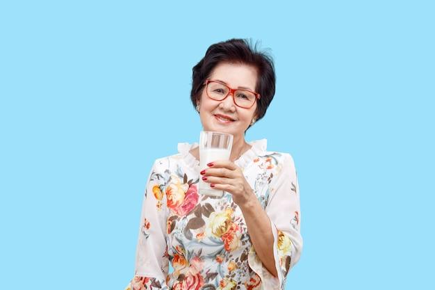 Старший женщина, держащая стакан молока, изолированные на белом