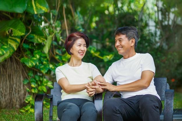 Средних лет пара расслабиться, сидя на скамейке на заднем дворе.