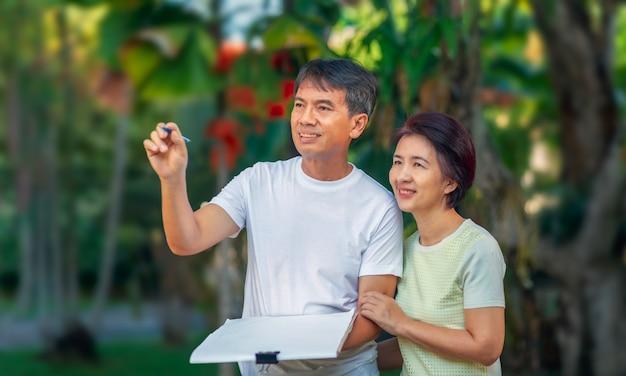 Азиатские пожилые пары говорить и проектирование сада планируют вместе в заднем дворе.