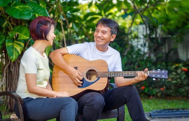 Середина постарела пары играя гитару пока ослабьте сидеть на стенде в задворк.