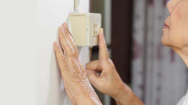 壁のスイッチでライトをオンにする高齢者の女性の手