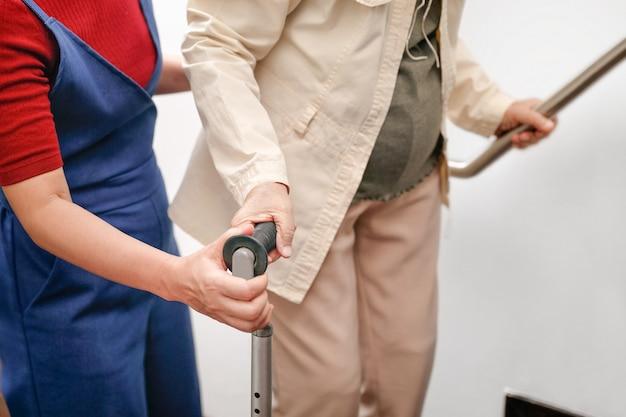 高齢者の女性が娘と自宅で杖を使用