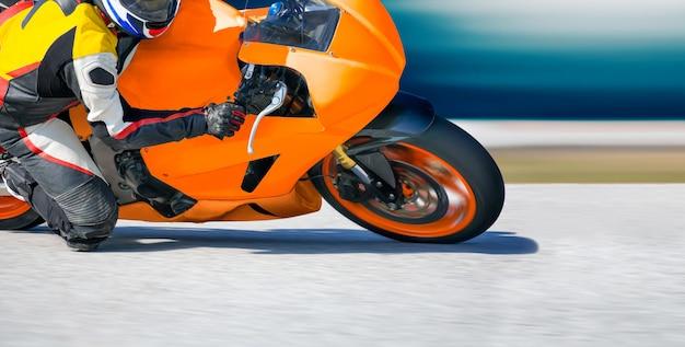 レーストラックの高速コーナーに傾いたオートバイ