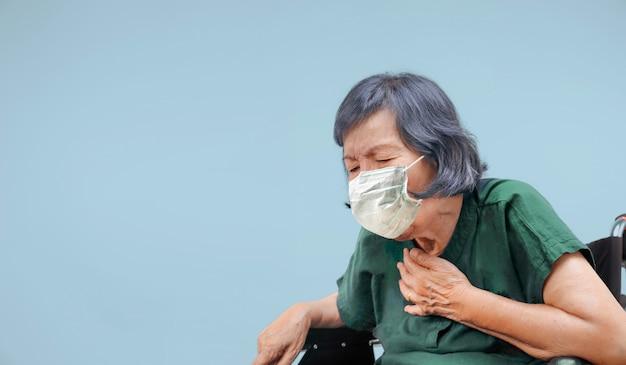 Пожилая женщина кашляет, задыхается на инвалидной коляске