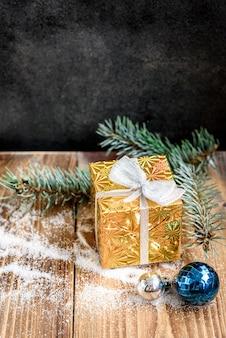 モミの枝、ギフトボックス、ボールとクリスマスの木製の背景。コピースペースとクリスマスの組成物。