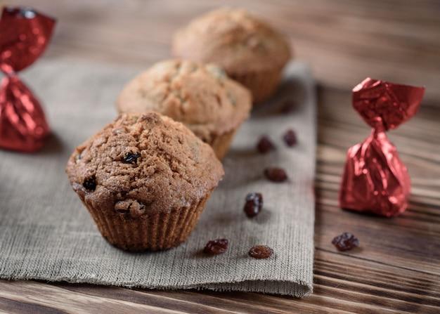 自家製のベーキング:木製の背景に亜麻布にレーズンのお菓子とカップケーキ。