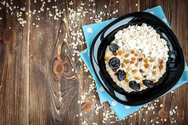 ドライフルーツと暗い木製のテーブルの上の黒い皿にカッテージチーズとオートミール。