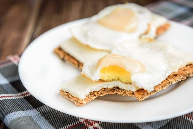ダークウッドのパリッとしたライ麦パンに柔らかいチーズと卵のサンドイッチ。