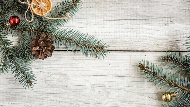 クリスマスのモミの枝と木製の背景にコーン。コピースペースとクリスマスの組成物。