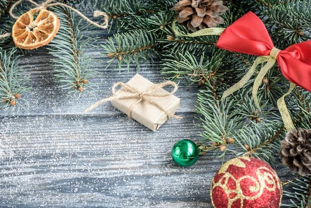 モミの枝、コーン、ボール、灰色の木の板にマシュマロとクリスマスや新年の装飾背景。