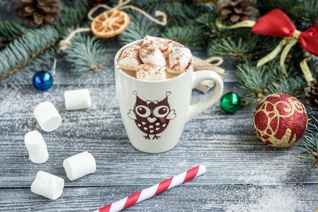 モミの枝、コーン、灰色の木製のテーブル上のボールとクリスマスの背景にホットチョコレートとマシュマロのマグカップ。