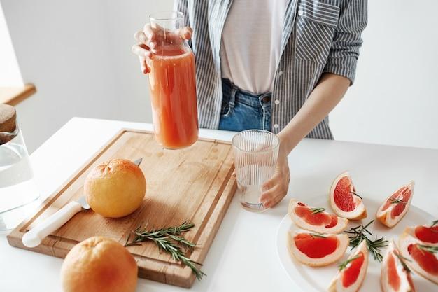朝食にグレープフルーツデトックススムージーとガラスの瓶を保持している少女のクローズアップ。健康的な栄養の概念。