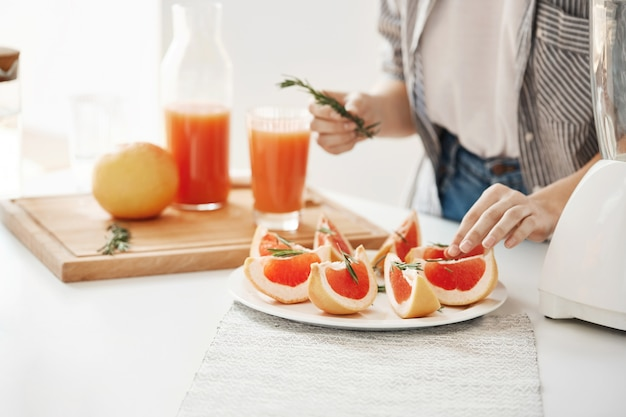 スライスしたグレープフルーツとローズマリーのプレートを飾る女の子のクローズアップ。フィットネス栄養の概念。コピースペース。