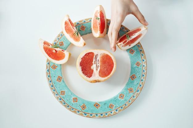 白い皿からグレープフルーツのスライスを取る女の子の手。上から。健康的な食事の栄養。