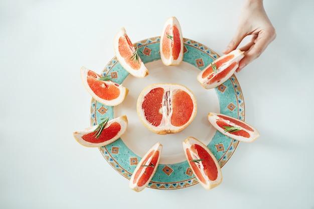 Рука девушки принимая кусок грейпфрута от белой плиты. сверху. здоровое диетическое питание.