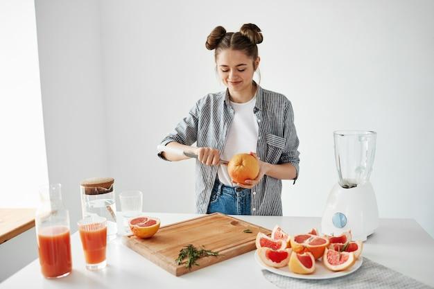 Девушка, делая грейпфрутовый сок или коктейль резки фруктов улыбается. концепция здорового образа жизни