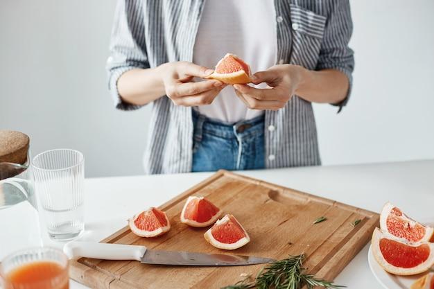 Закройте вверх девушки держа часть грейпфрута над белой стеной. концепция здорового питания