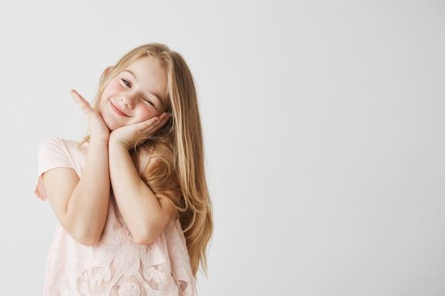 美しいブロンド少女は、ピンクのかわいいドレスで彼女の手でウインク、ポーズ、顔に触れる笑顔します。幸せそうに見えて喜んでいる子供。コピースペース。