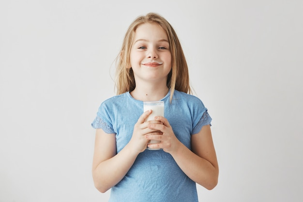 Маленькая милая девушка со светлыми волосами в синей футболке с молоком падает на лице, рады начать свой день с большой стакан здорового напитка.