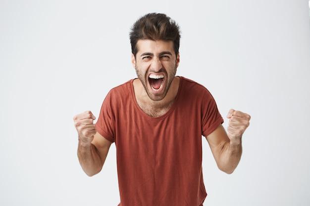 Счастливый положительный возбужденный молодой человек сжимает кулаки и кричит, надев повседневную футболку, рад слышать хорошие новости, празднуя свою победу или успех. жизненные достижения, цели и концепция счастья