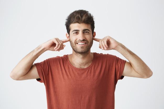 目を閉じて指で耳を塞いでいるイライラした若い男性白人の肖像は、大きな音を立てたり、ストレスの多い不快な状況や対立を無視したりできません。人間の否定的な感情