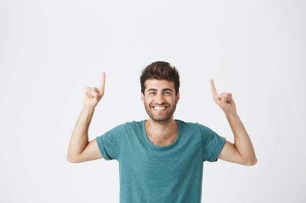 Проверьте это обрезанный снимок привлекательного красивого взволнованного молодого человека в синей футболке, указывающего пальцами вверх с удивленным взглядом, с веселым и счастливым выражением лица. бродли улыбается