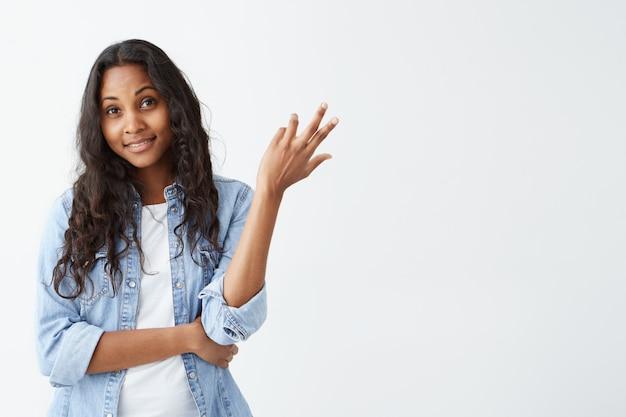 白い壁に分離された困惑を探している疑わしいアフリカ系アメリカ人の若い女性の肖像画。混乱して不確実なデニムシャツに身を包んだ心地よく見える暗い肌の女性