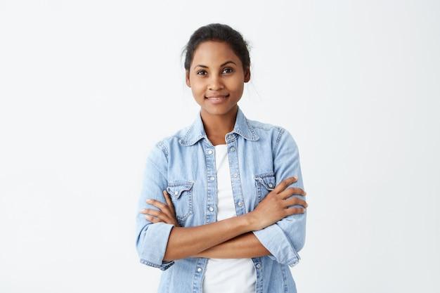 立っている黒い髪の落ち着いたアフリカ系アメリカ人女性の写真は白い壁にポーズをとって誠実で楽しい笑顔を持っている手を渡った。彼女の人生を喜んで幸せな浅黒い肌の女性。