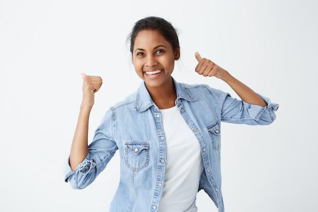 親指ジェスチャー、彼女のような表現、アイデアやプロジェクトの承認を示す黒い髪の陽気な熱狂的な美しいアフリカ系アメリカ人女性が広く笑っています。